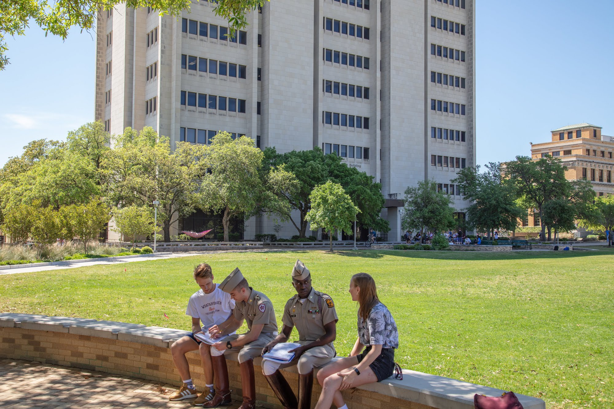 students studying on bench in front of O&M building